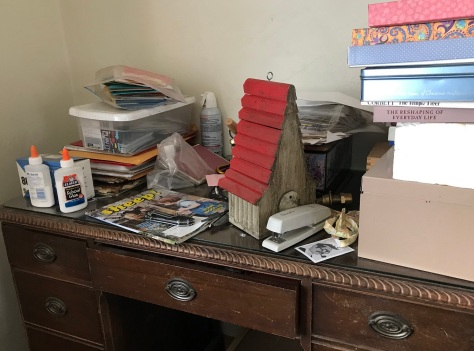 Photo of desk covered with stationary, a stapler, bird house, magazine, books, and other random items.